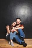 Paare, die nahe der Wand sitzen Stockfoto