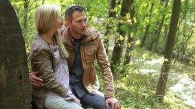 Paare, die nahe großem Klotz und dem Küssen sitzen stock footage
