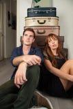 Paare, die nahe Koffern sitzen Lizenzfreie Stockfotografie
