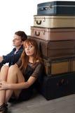 Paare, die nahe Koffern sitzen Lizenzfreie Stockbilder
