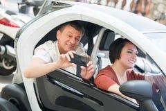 Paare, die nahe twizy elektrischem stehen Lizenzfreie Stockfotos