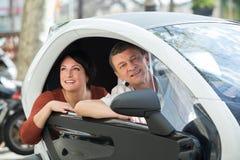 Paare, die nahe twizy elektrischem stehen Stockfoto
