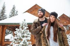 Paare, die nahes Blockhaus im Schneewetter stehen Stockbilder
