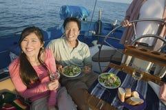 Paare, die Nahrung auf der Yacht essen Stockfotos