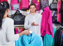Paare, die neue Sportkleidung im Sportspeicher wählen Stockfotos