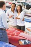 Paare, die neues Auto vom Verkäufer aufheben stockfotos