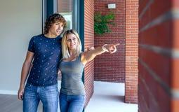Paare, die neues Haus aufpassen, um es zu kaufen lizenzfreie stockfotos