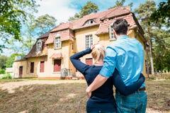 Paare, die neues Haus betrachten stockfotografie
