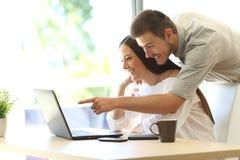 Paare, die online in einem Laptop zu Hause suchen lizenzfreies stockbild