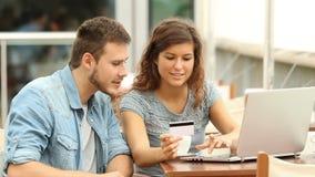 Paare, die online in einer Kaffeestube kaufen stock video footage