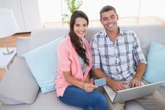Paare, die online unter Verwendung des Laptops und der Kreditkarte kaufen Lizenzfreie Stockfotografie