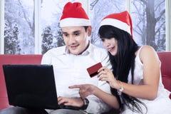 Paare, die online am Weihnachtstag zahlen Lizenzfreies Stockfoto