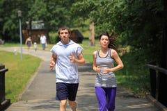 Paare, die in Park laufen Lizenzfreie Stockfotografie