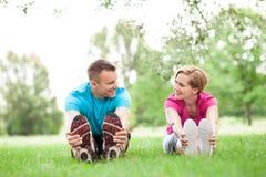 Paare, die in Park vor Training ausdehnen Lizenzfreie Stockfotos
