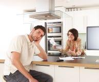 Paare, die persönliche Finanzen in der Küche behandeln stockbilder