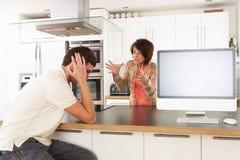 Paare, die persönliche Finanzen in der Küche behandeln Stockfotografie