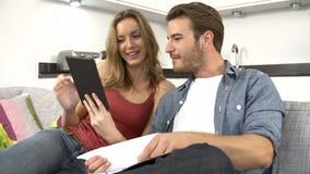 Paare, die persönliche Finanzen unter Verwendung Digital-Tablets überprüfen stock footage