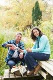 Paare, die Picknick im Herbst genießen Stockfotos