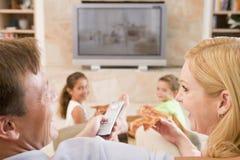 Paare, die Pizza vor Fernsehapparat genießen Stockfoto