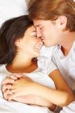 Paare, die Romance auf Bett zeigen Stockbild