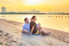 Paare, die romantischen Sonnenaufgang auf dem Strand aufpassen Stockbilder