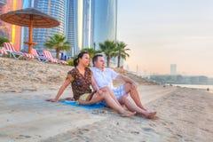 Paare, die romantischen Sonnenaufgang auf dem Strand aufpassen Stockfotografie