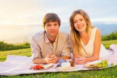 Paare, die romantisches Sonnenuntergang-Picknick genießen Stockfoto