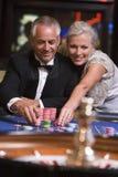 Paare, die am Roulettetisch spielen Stockbild