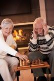 Paare, die Schach im cosy Wohnzimmer spielen Stockfotografie