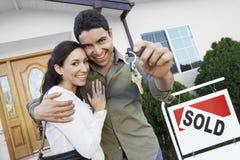 Paare, die Schlüssel ihres neuen Hauses zeigen Stockfotos