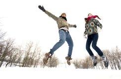 Paare, die in Schnee springen lizenzfreie stockfotos