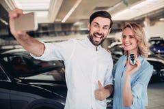 Paare, die selfie auf Smartphone mit Schlüsseln nehmen stockfotos