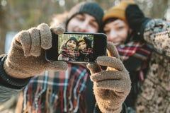 Paare, die selfie im Winterwald machen Stockfotos