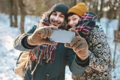 Paare, die selfie im Winterwald machen Lizenzfreie Stockfotos