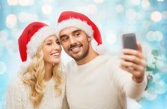 Paare, die selfie mit Smartphone am Weihnachten nehmen Lizenzfreies Stockbild