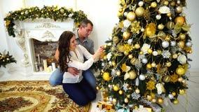 Paare, die sich zusammen für bevorstehenden Feiertag und Umarmung im hellen Raum auf Hintergrund des festlichen Weihnachtsbaums v stock video
