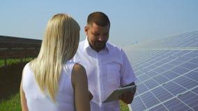 Paare, die in Solarkraftwerk sprechen stock video footage