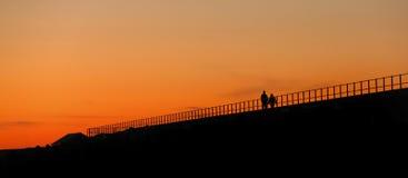 Paare, die am Sonnenuntergang gehen Lizenzfreies Stockbild