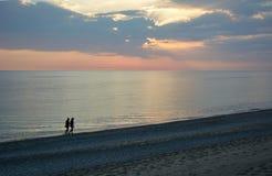 Paare, die in Sonnenuntergang gehen Stockbilder