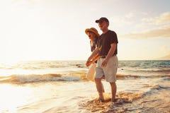 Paare, die Sonnenuntergang am Strand genießen Stockbilder