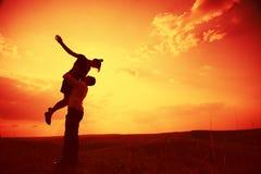 Paare, die am Sonnenuntergang umfassen lizenzfreie stockfotografie
