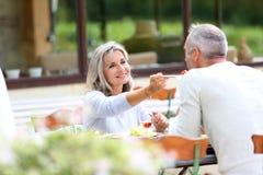 Paare, die am sonnigen Tag zu Mittag essen Lizenzfreie Stockbilder
