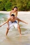 Paare, die Spaß durch den Strand haben Lizenzfreies Stockbild