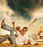 Paare, die Spaß auf dem Strand haben Stockfotos