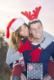 Paare, die Spaß draußen mit Weihnachtshüten haben Lizenzfreies Stockfoto