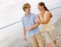 Paare, die am Strand umarmen Stockfotografie