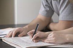 Paare, die Sudoku in der Zeitung am Schreibtisch lösen Stockbilder