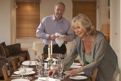 Paare, die Tabelle für ein Abendessen vorbereiten lizenzfreies stockfoto