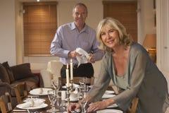 Paare, die Tabelle für ein Abendessen vorbereiten Stockfoto