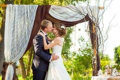 Paare, die unter dekorativem Hochzeitsbogen küssen stockfotos